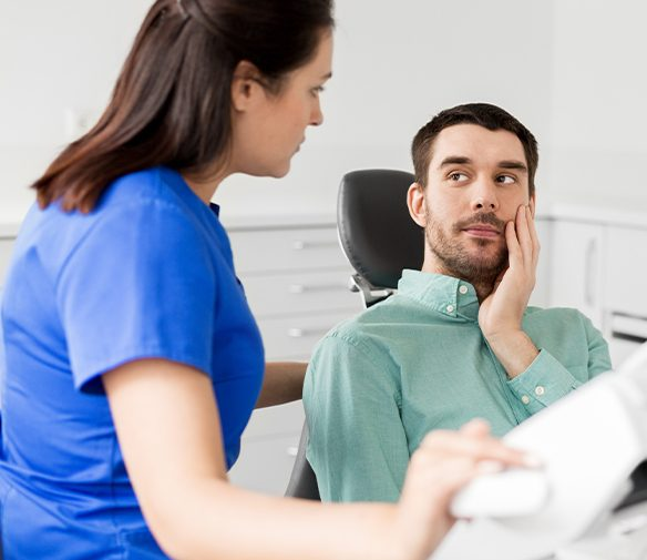 Man at emergency dentistry visit holding jaw